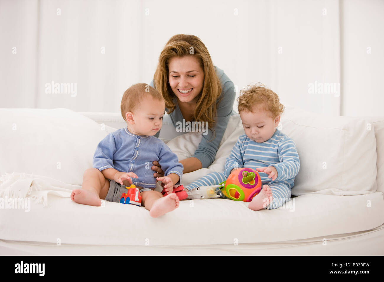 Woman playing with her son and daughter on a couch Stock Photo