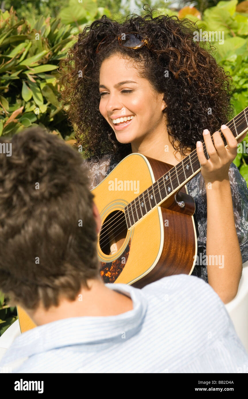 Woman playing a guitar in front of a man - Stock Image