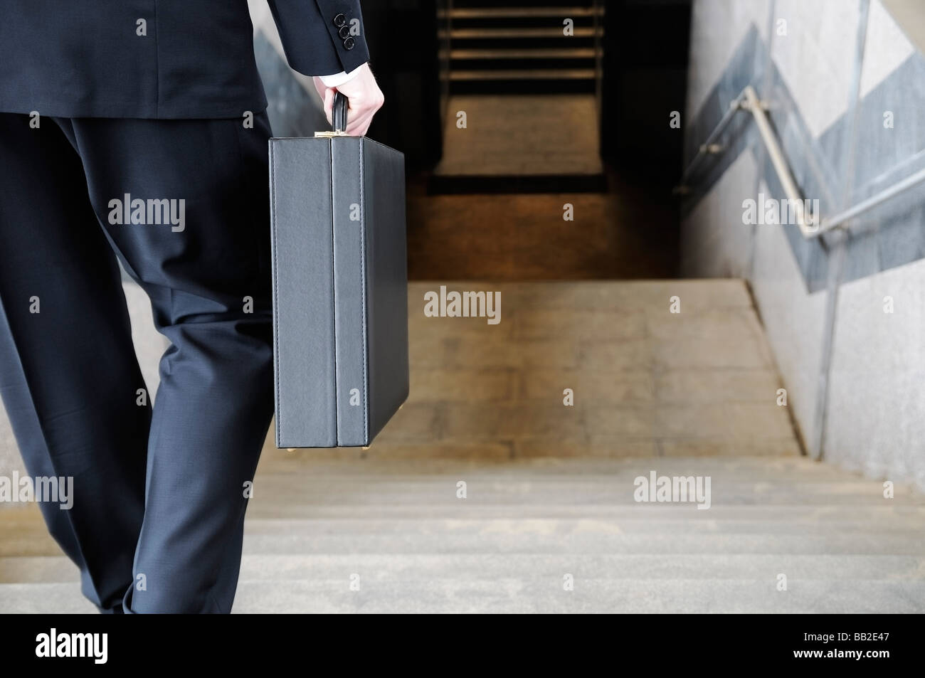 Businessman Carrying a Briefcase Going Down Stairs to a Subway Station Rear View - Stock Image