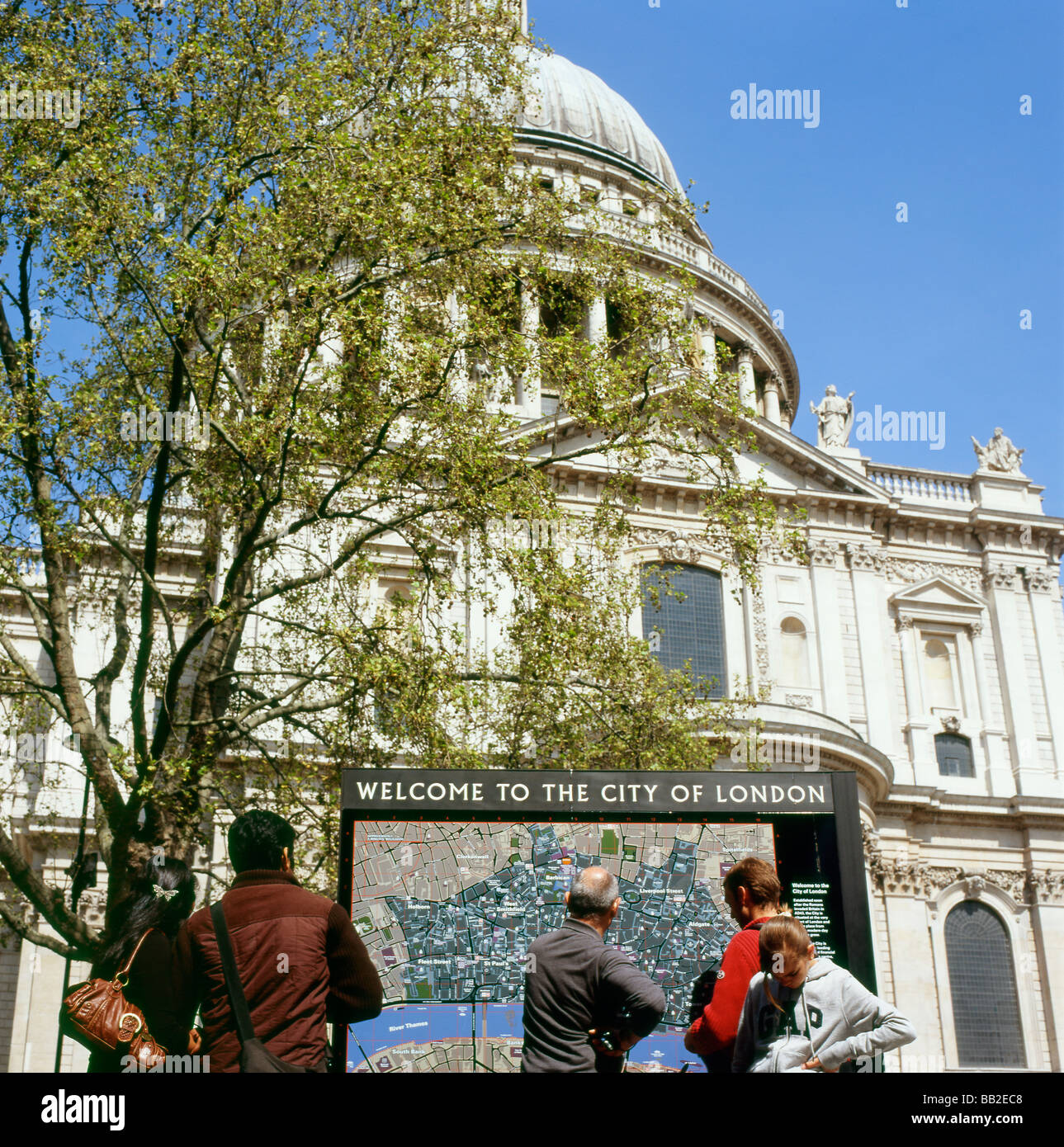 Tourists near St Paul s Cathedral reading a map of London England UK