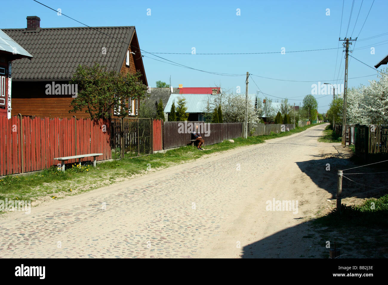 An old woman sitting on a bench in Soce village, Poland - Stock Image