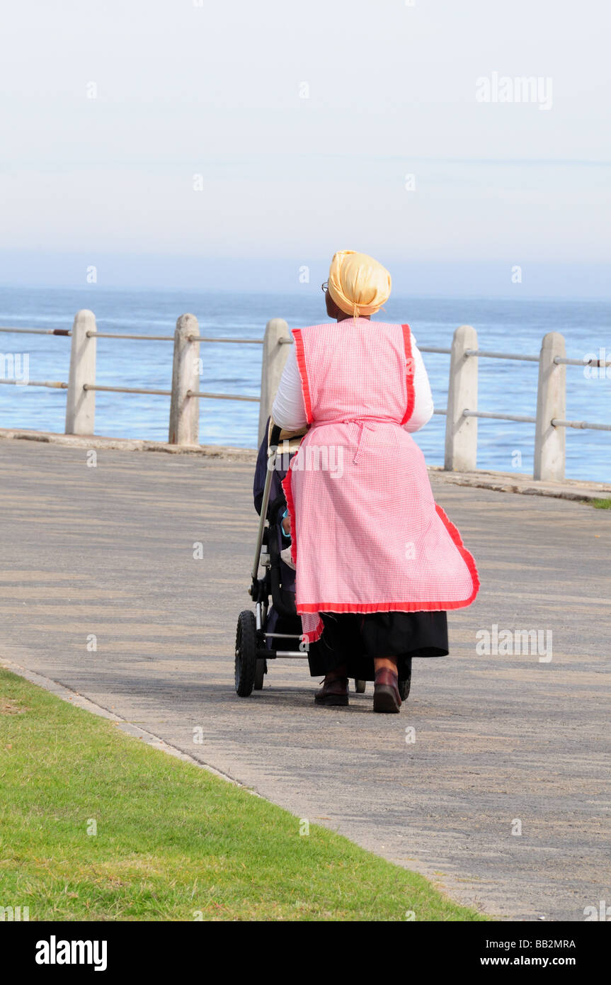African nanny taking a baby for a walk along Green Point Cape town South Africa - Stock Image