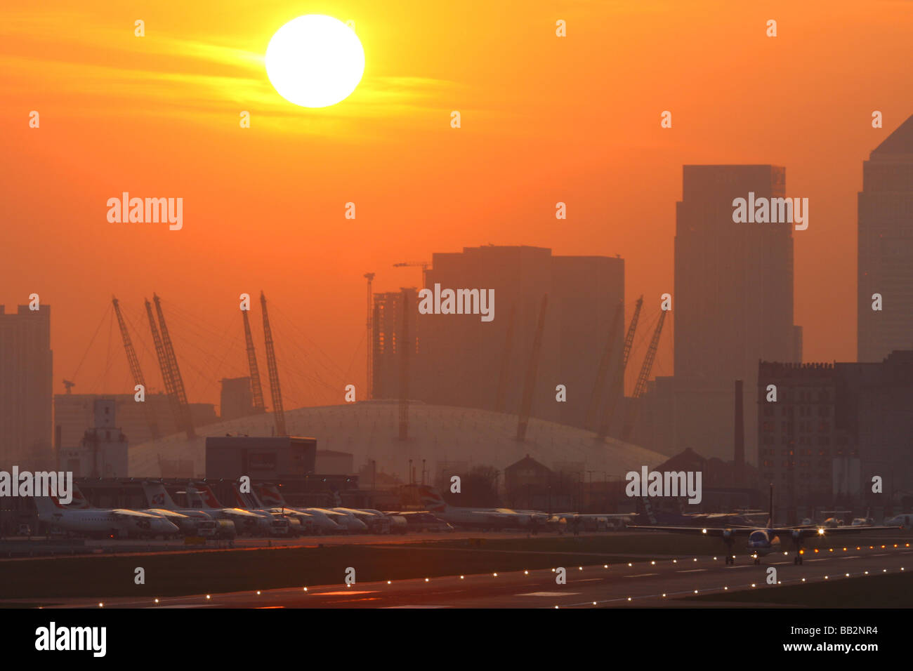 Evening overview of crowded London City Airport with 02 Arena (Millennium Dome) in the background - Stock Image