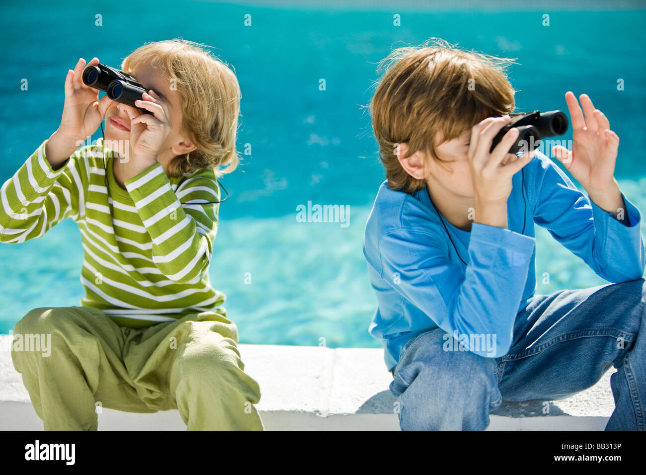 Two boys looking through binoculars at the poolside - Stock Image