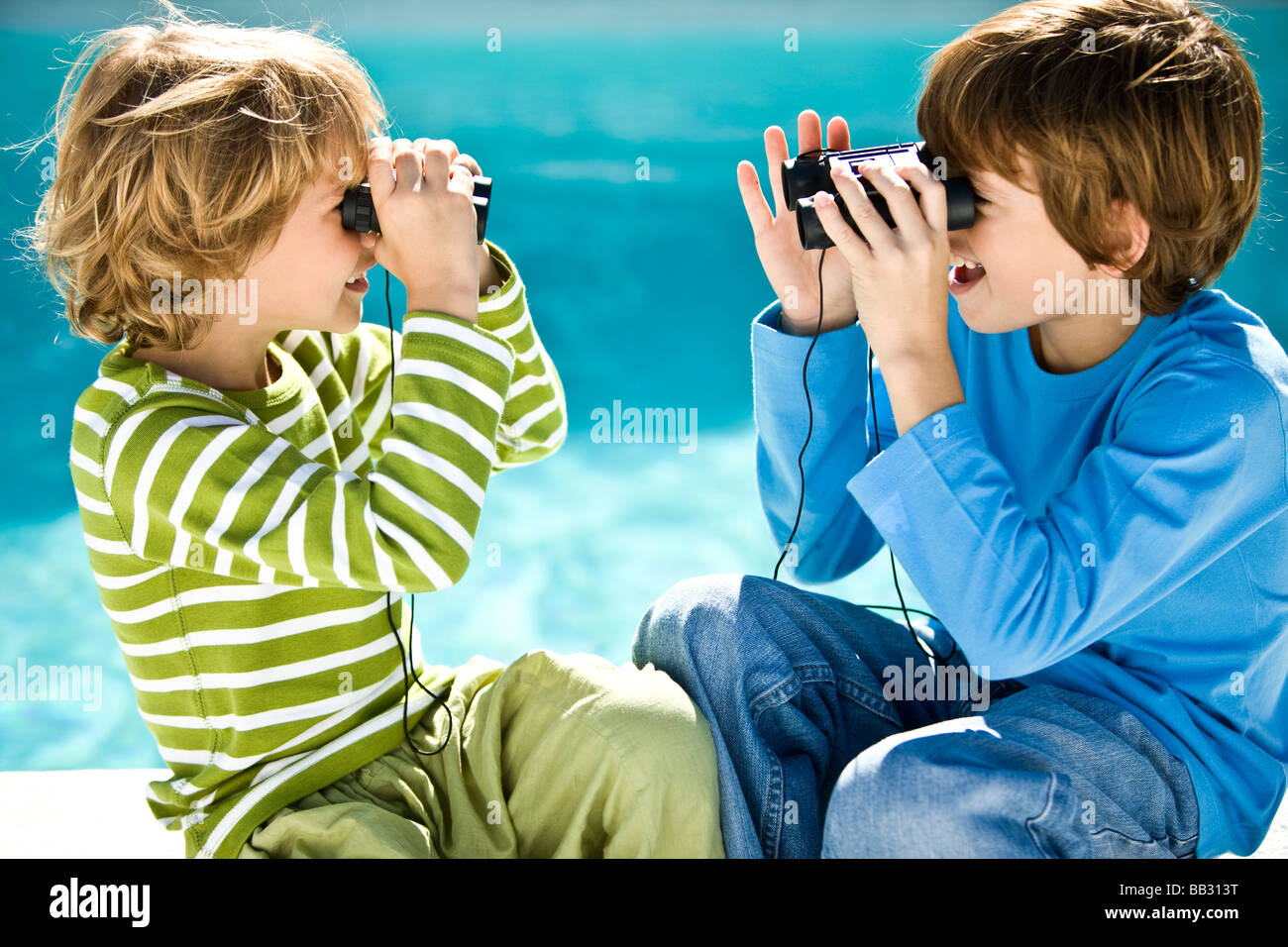 Two boys looking at each other through binoculars at the poolside - Stock Image