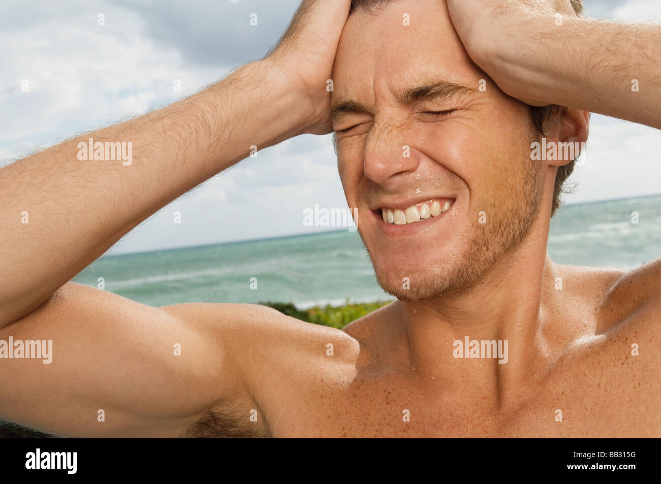Man holding his head in pain on the beach - Stock Image