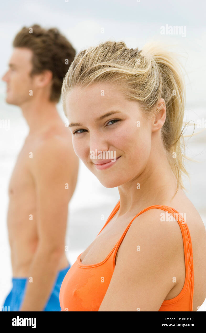 Portrait of a woman standing with a man on the beach - Stock Image