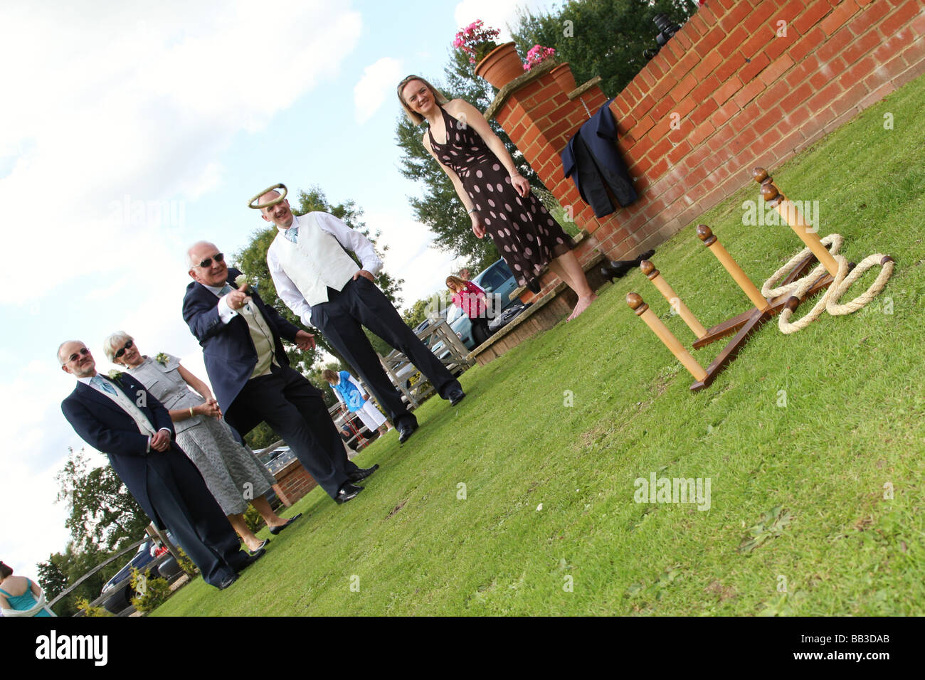 Wedding guests outside playing hoops game at reception - Stock Image