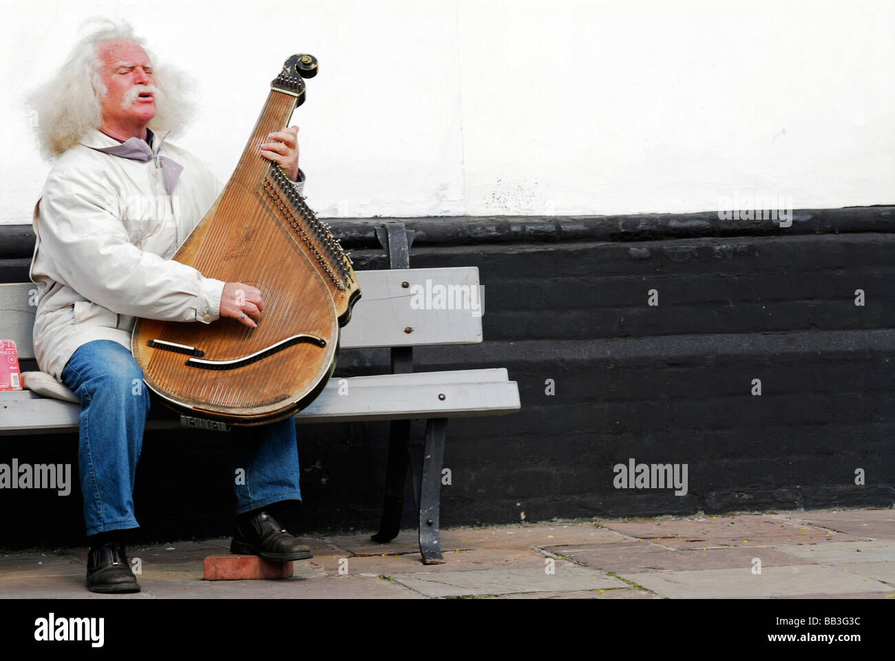 UKRAINE, Kiev. Old man with white long & fuzzy hair sitting on a bench, carrying a lute, his left foot resting - Stock Image
