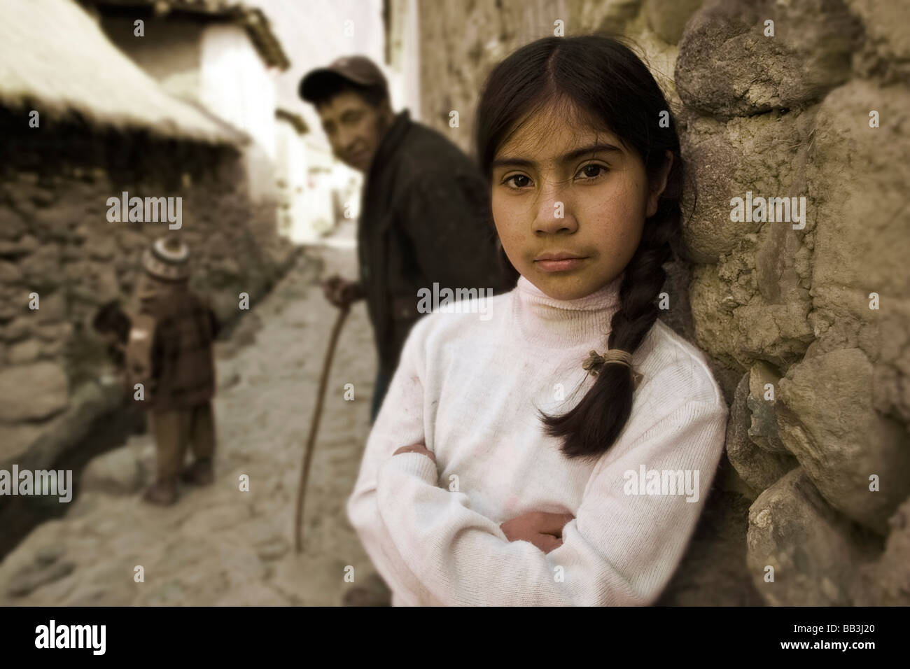 Girl with father and younger siblings in background, Ollantayambo, Peru. - Stock Image