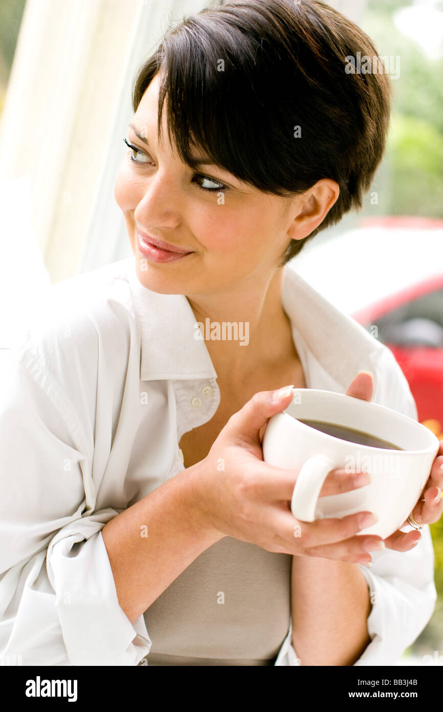 Woman relaxing with warm drink - Stock Image