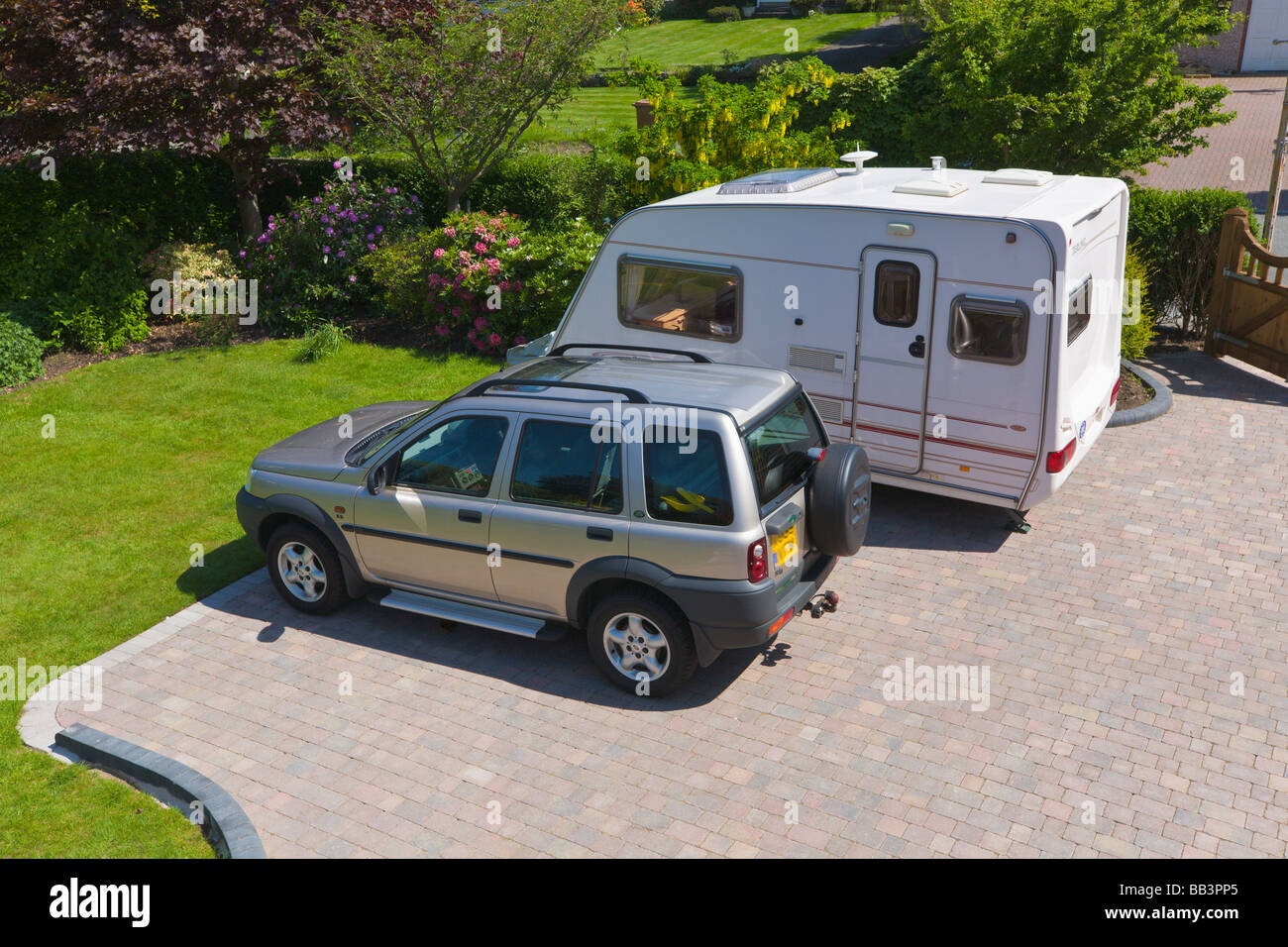 Car and caravan parked on driveway of a house - Stock Image