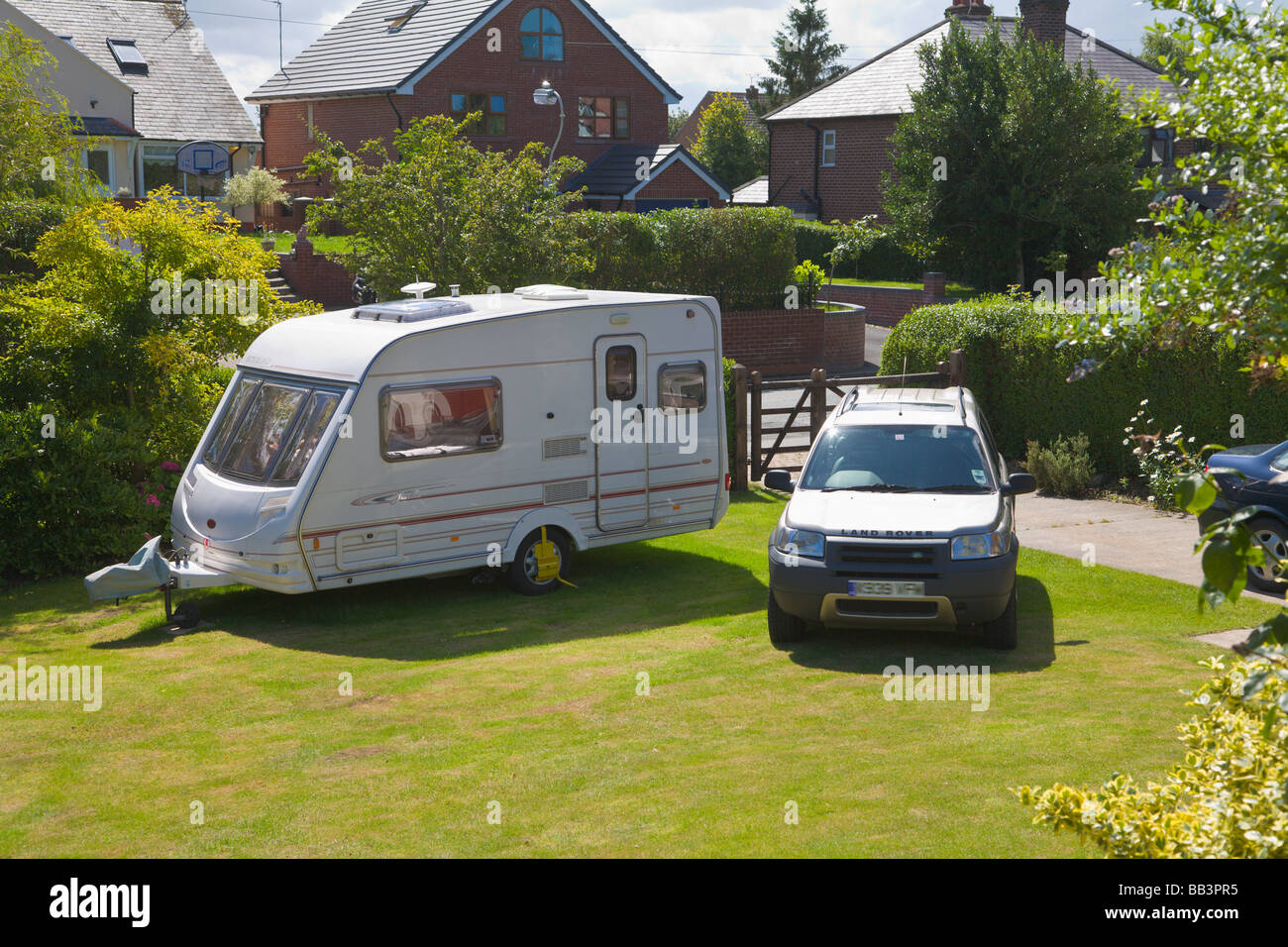 Car and caravan parked on front lawn of a house - Stock Image
