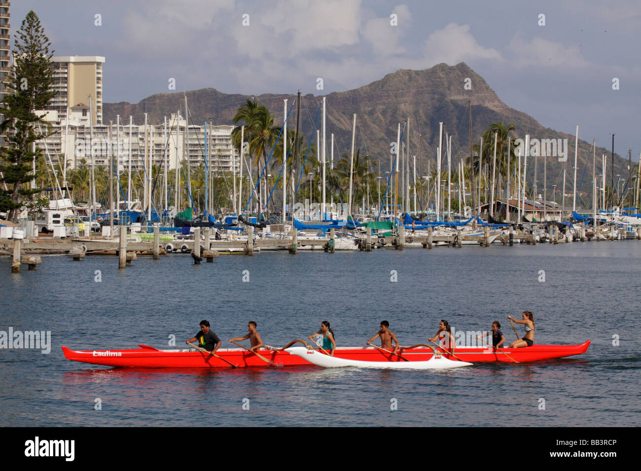 High school students practicing in outrigger canoes Ala Moana Beach Park Waikiki Oahu Hawaii USA - Stock Image