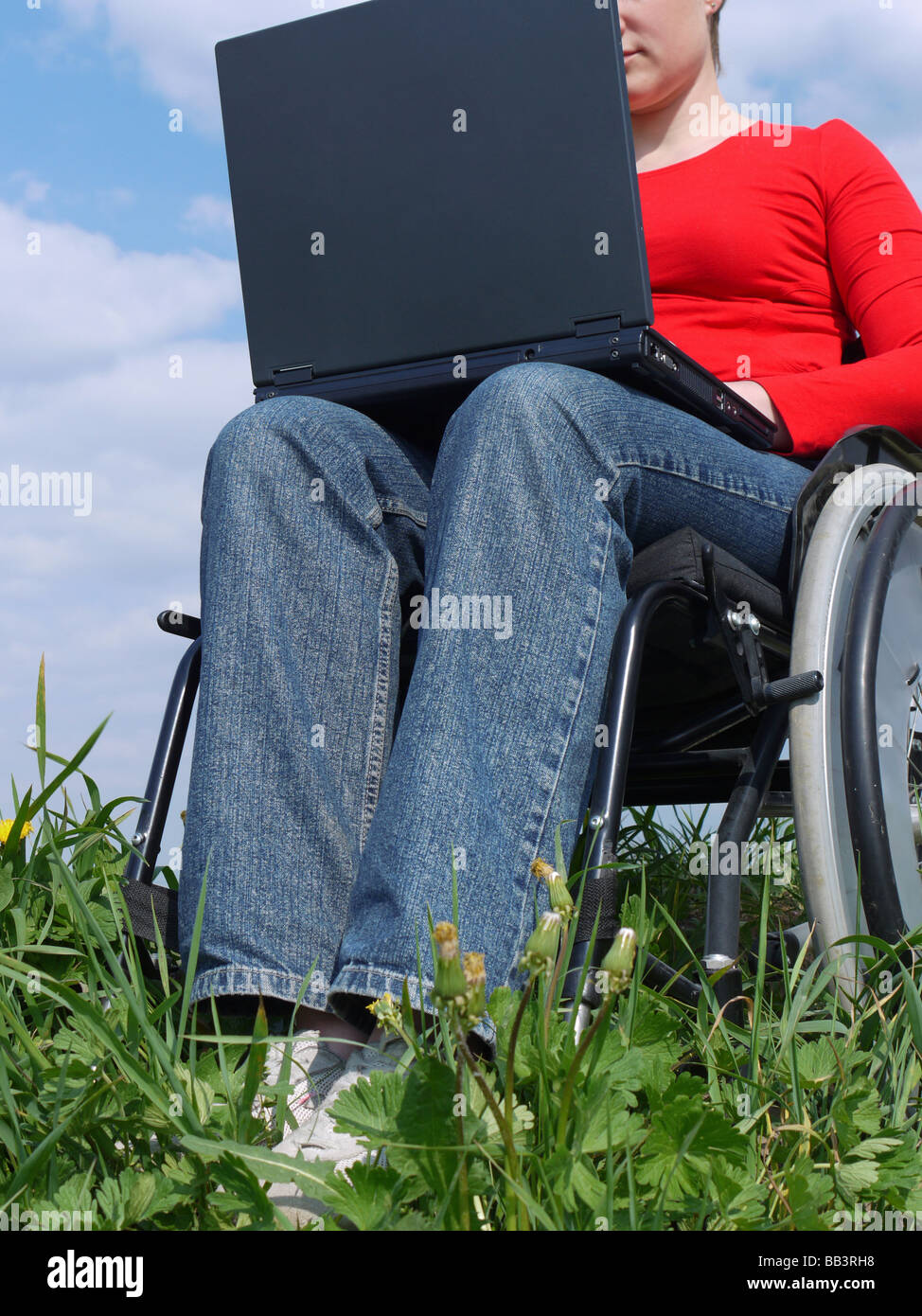 Handicapped woman on wheelchair using laptop outdoors - Stock Image