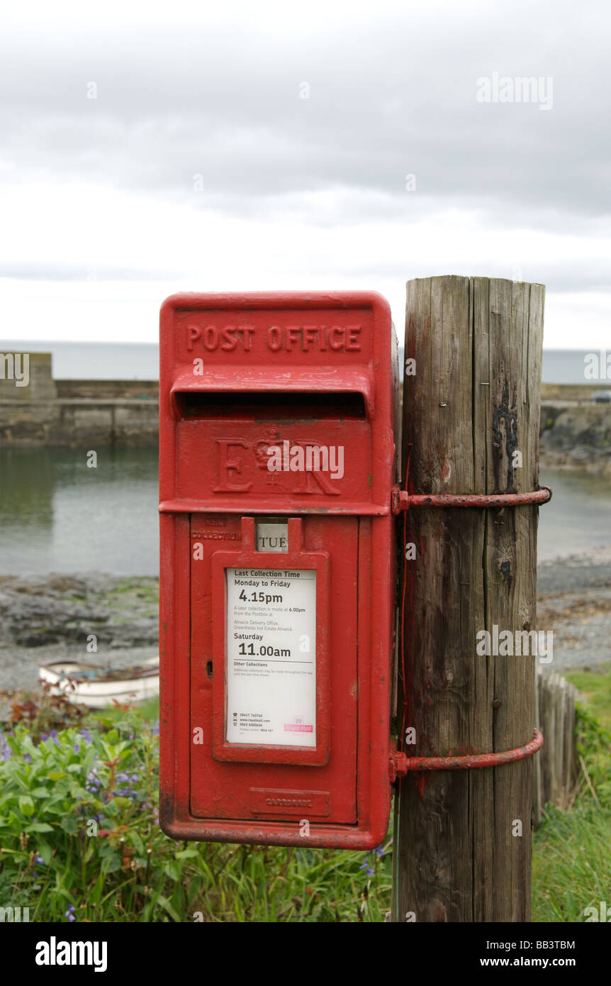 A red post box in Craster harbour, Northumberland - Stock Image