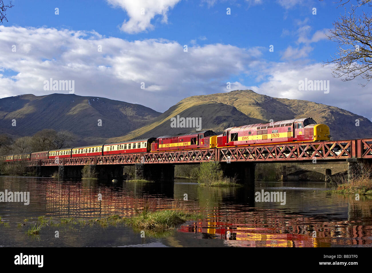 Railtour / Landcruise on the West Highland Line from Oban to Fort William seen crossing Loch Awe. - Stock Image