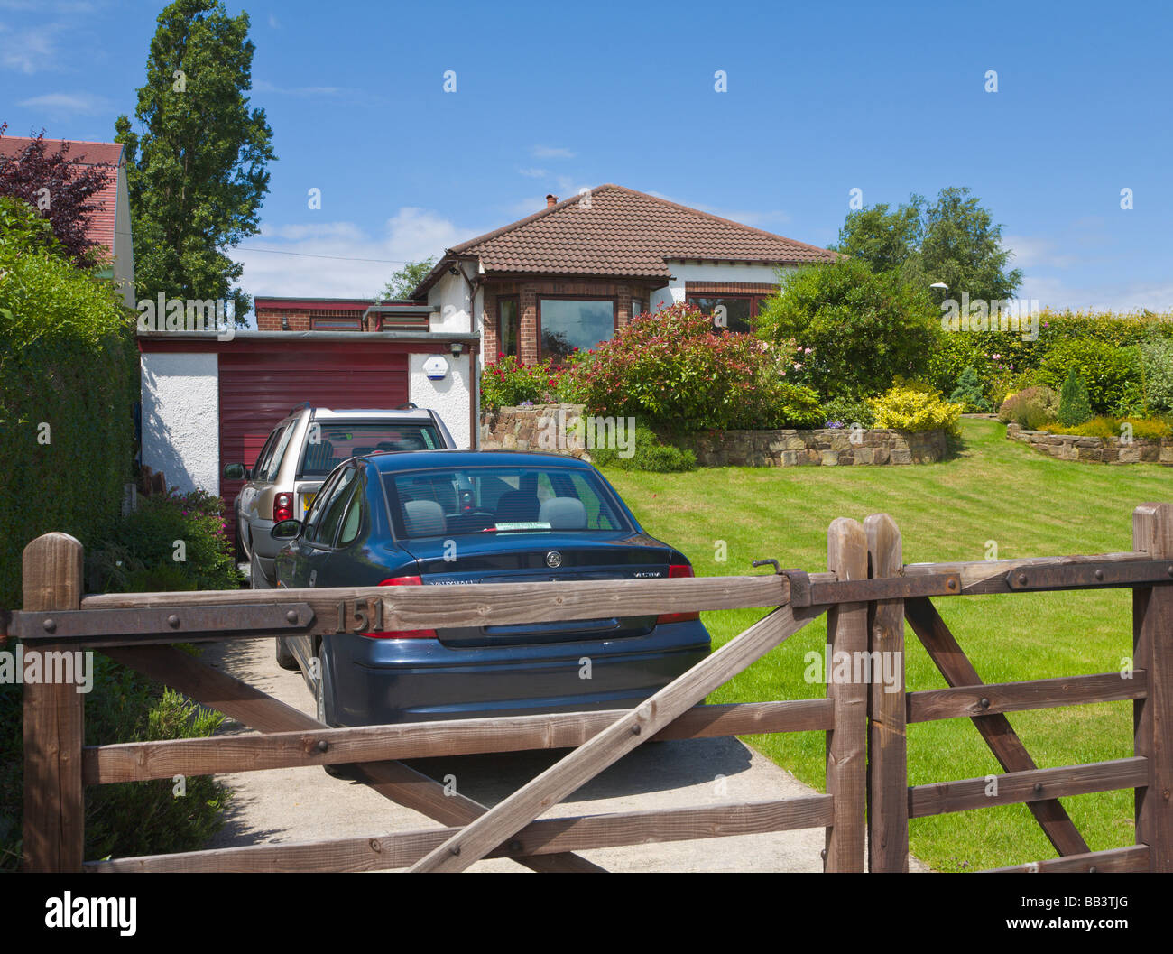 Driveway and garage of detached bungalow with parked cars - Stock Image