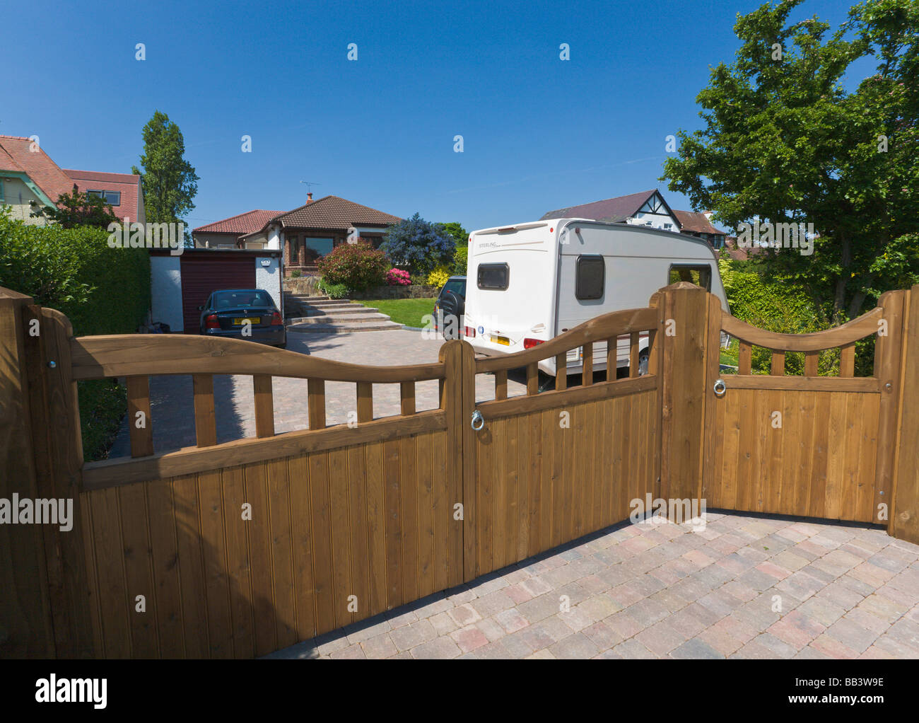 Driveway and garage of detached bungalow with parked cars and caravan - Stock Image