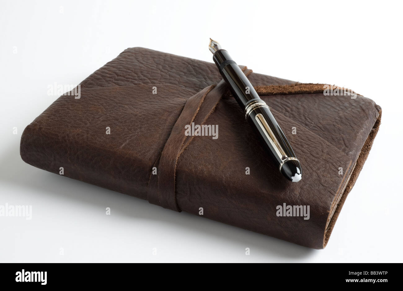 Tuscan leather bound journal and fountain pen on plain white background. - Stock Image