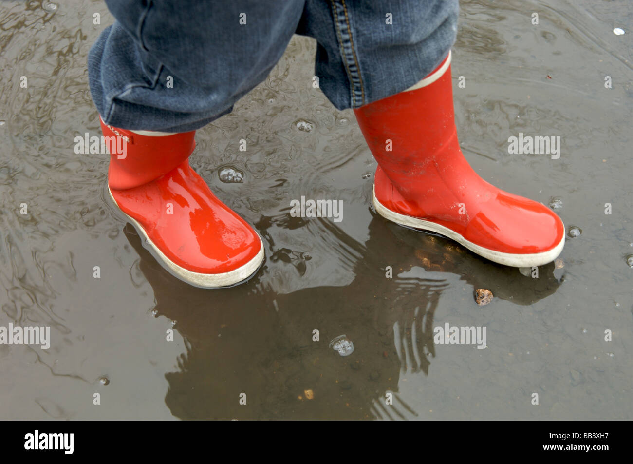 A young child in red wellington boots