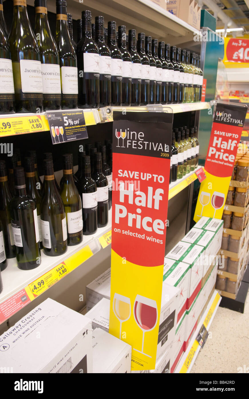 Cheap alcohol (bottles of wine) for sale on the shelves of a uk supermarket (Tesco) selling at half price - Stock Image