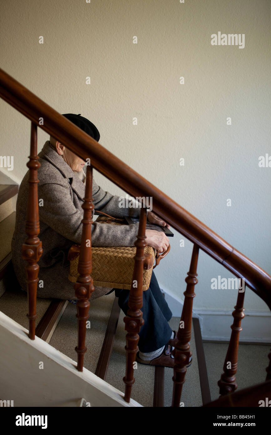 Senior sitting with a suitcase on the stairs - Stock Image