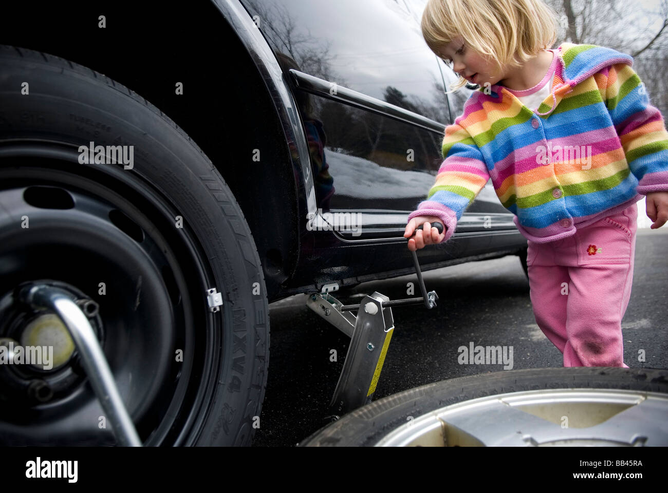 2-3 year old girl changing a flat tire, Cumberland, Maine. - Stock Image