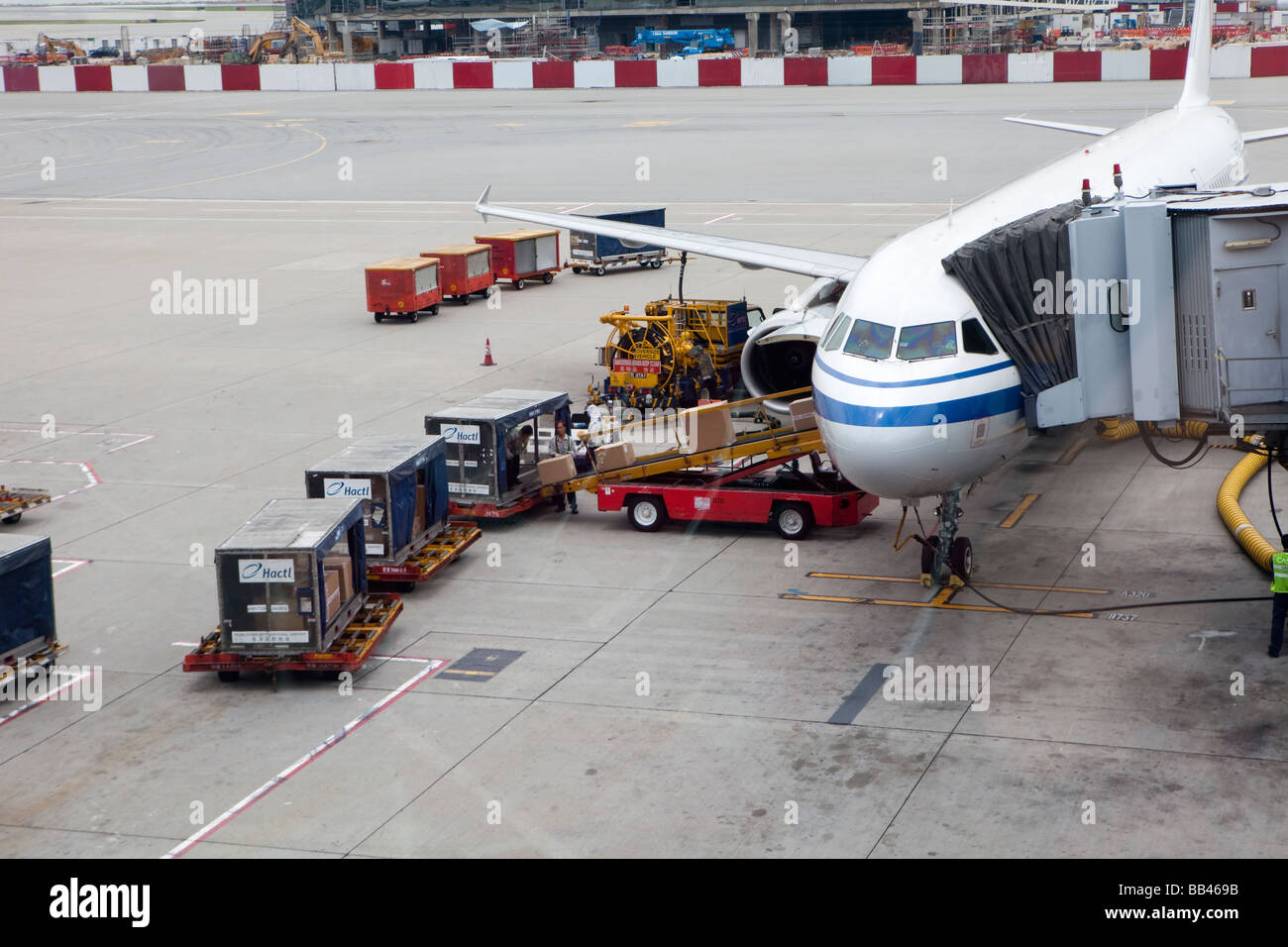 Workers prepare a plane at the Hong Kong International Airport - Stock Image