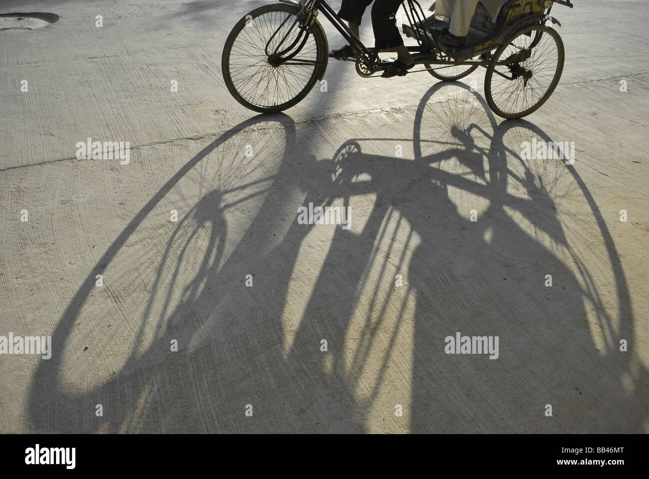 Long shadow of tricycles - Stock Image