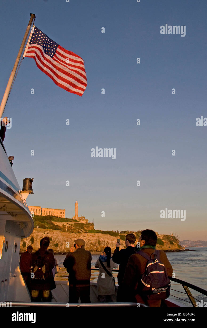 On a San Francisco Bay tour boat, a group of young tourists, under a waving American Flag, photograph Alcatraz Island - Stock Image