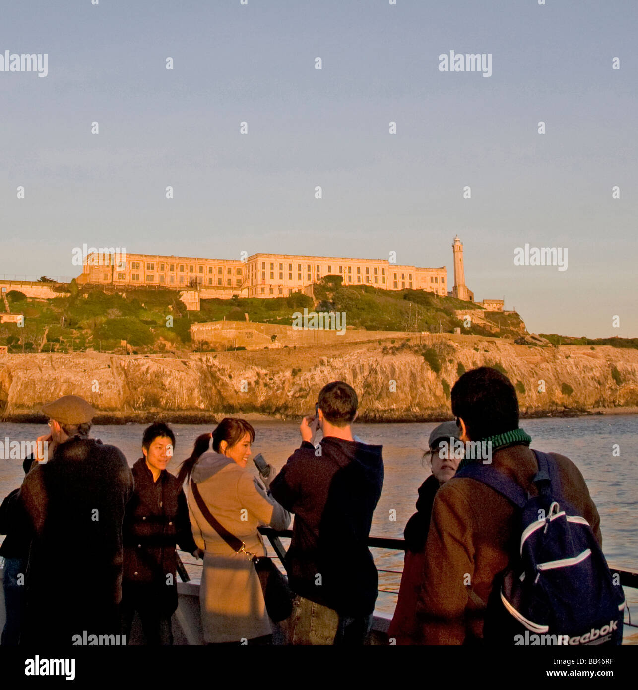 On a San Francisco Bay tour boat,a group of young Asian tourists , photograph Alcatraz Island and prison - Stock Image