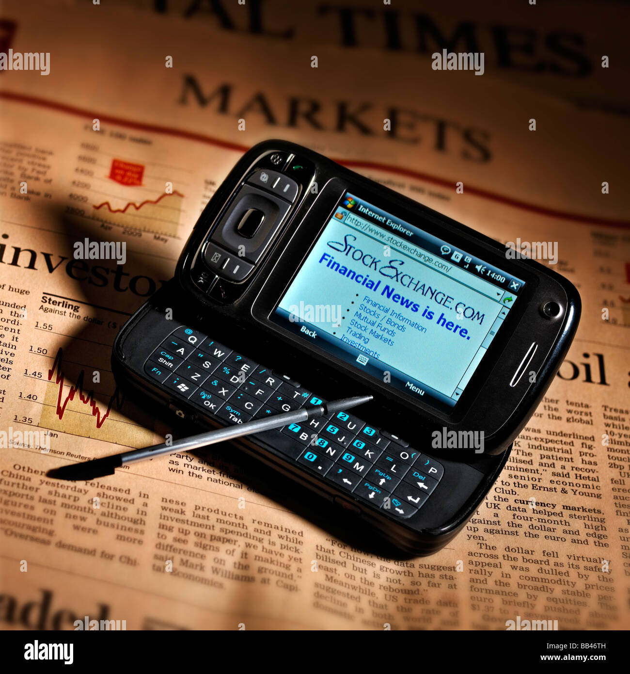MOBILE PHONE PDA INTERNET ACCESS WITH NEWSPAPER FINANCIAL PAGE - Stock Image
