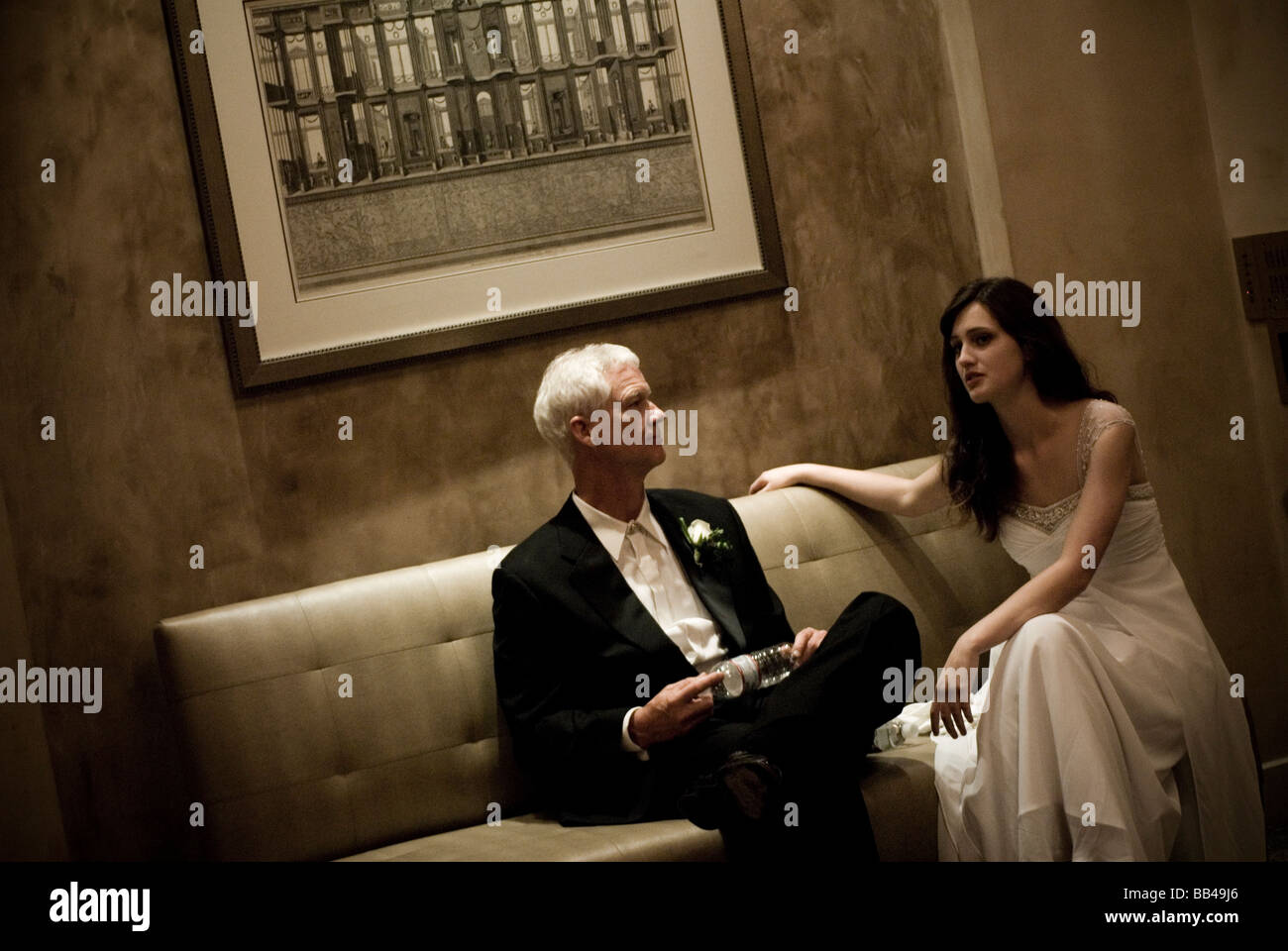 A debutante and her father relax on a couch in a hotel lobby in La Jolla, California. - Stock Image