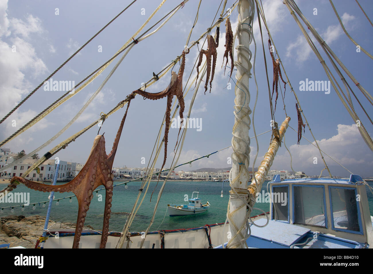 Europe, Greece, Mykonos, Hora. Octopi drying on the rigging of a boa with harbor in background. - Stock Image