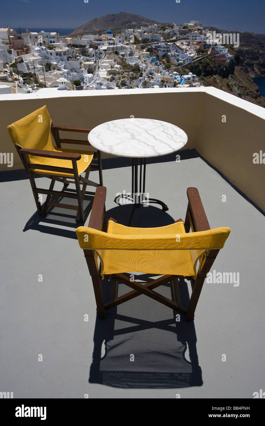 Europe, Greece, Santorini. Yellow Patio Chairs And White Table Overlooking  Town Of Firostefani.