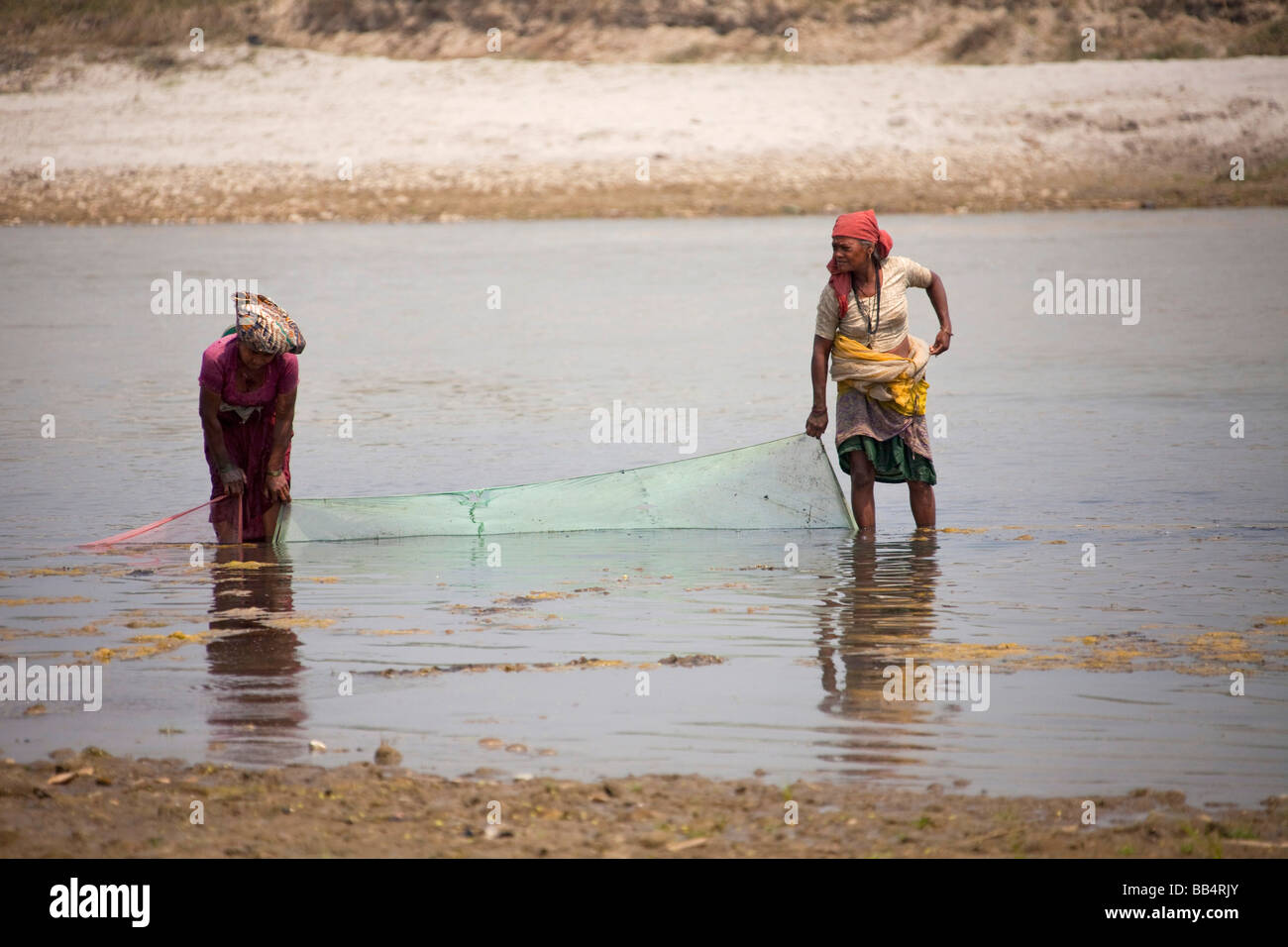 local Women fishing with net waste high in river water