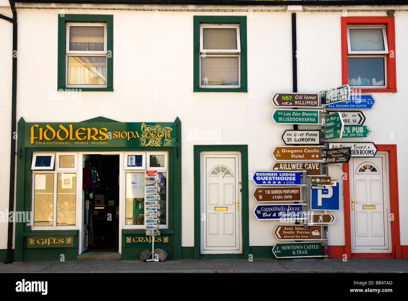 Europe, Ireland, Ballyvaughan. Store fronts and an informative sign post in the village center. - Stock Image