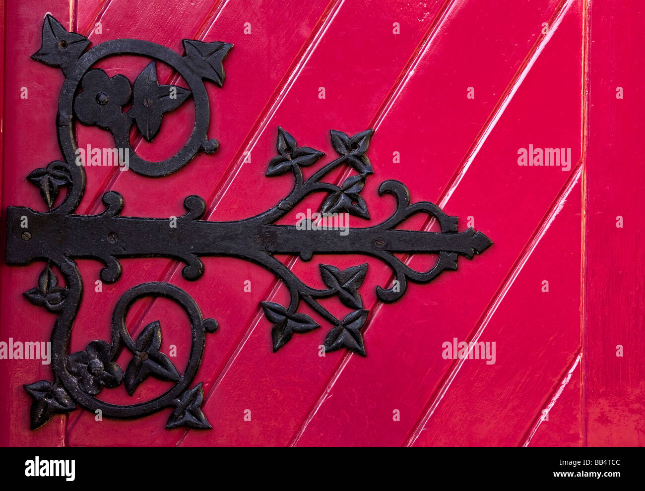 Europe, Ireland, Ennis. A decorative black hinge on a bright red door of the new Franciscan Friary for monastics. - Stock Image