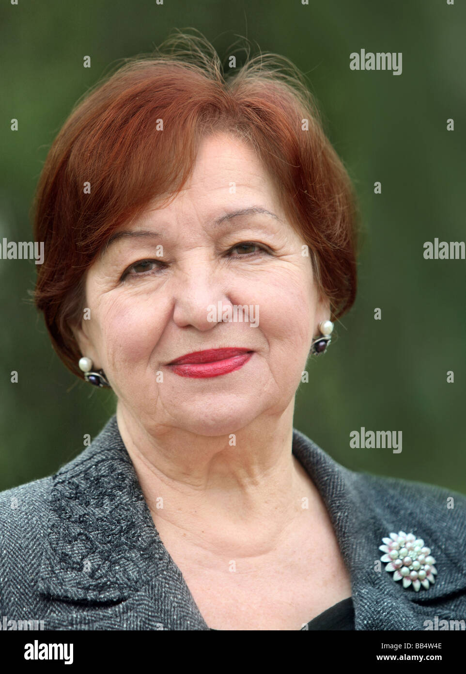 Portrait of a smiling woman in her seventies - Stock Image