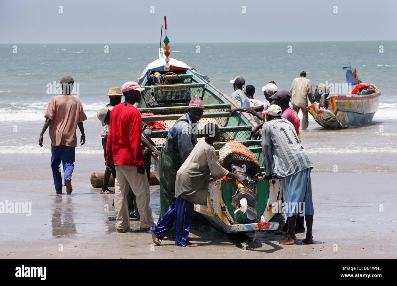 Fishermen bring a boat up onto the shore at Kap Skirring, Senegal - Stock Image