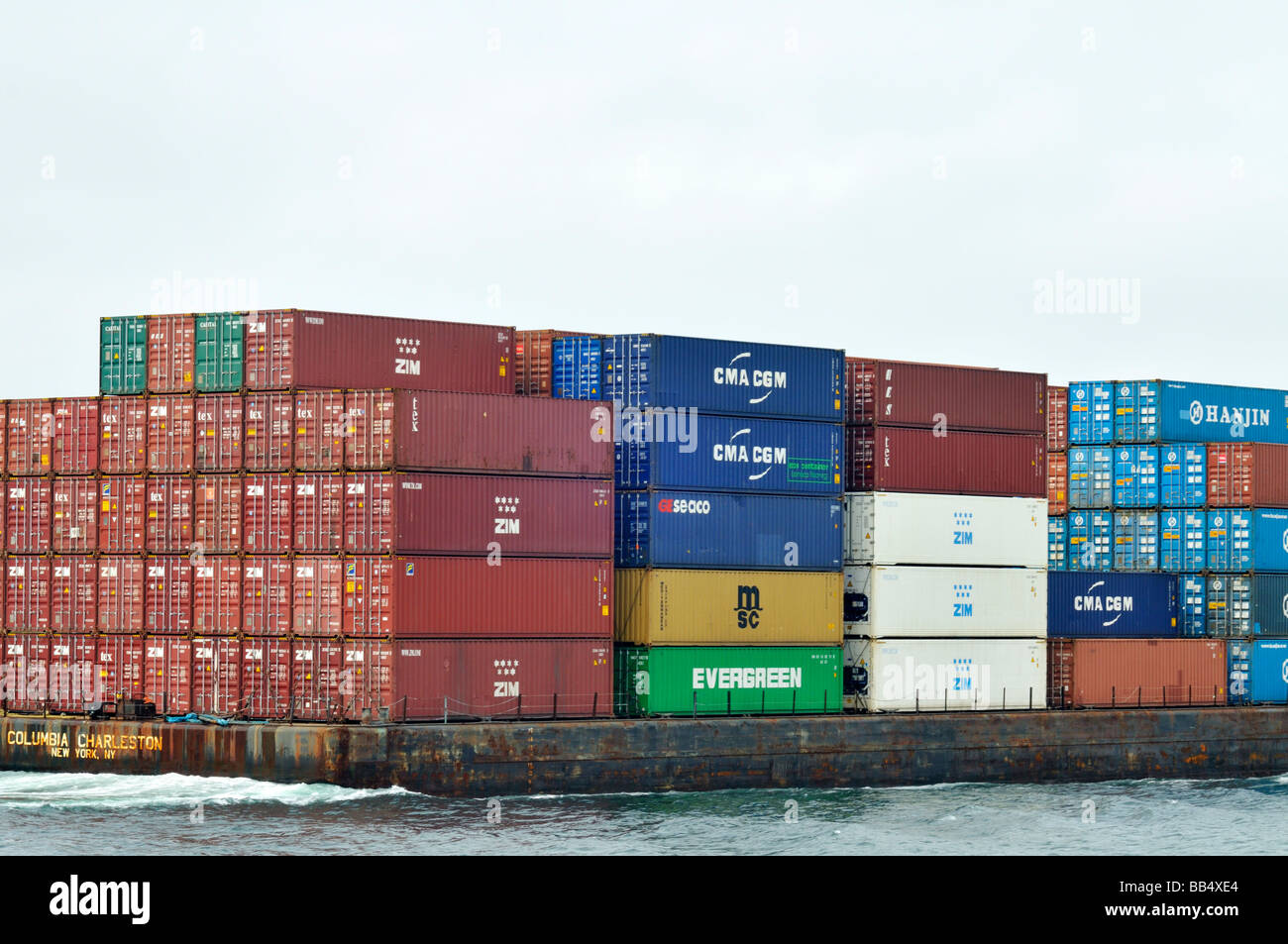 Container barge loaded with metal shipping containers in ocean USA Stock Photo
