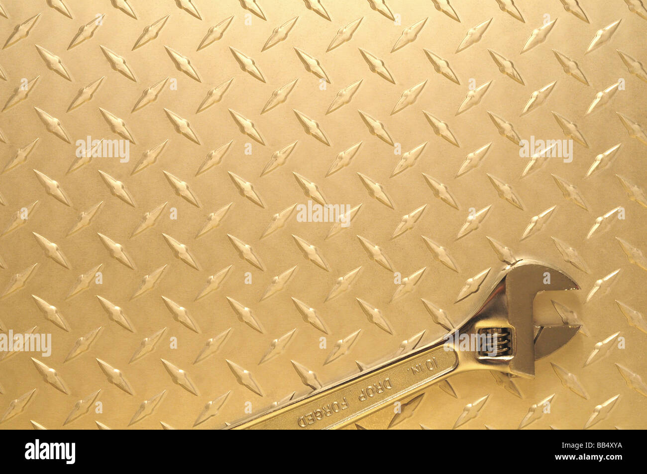 Crescent wrench on diamond plate steel background - Stock Image