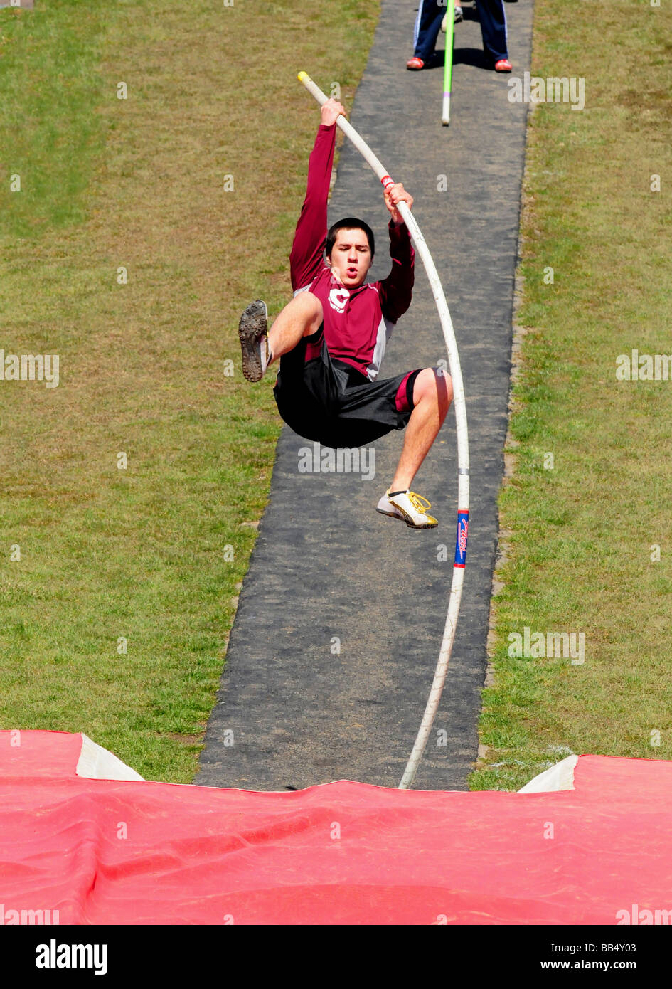A pole vaulter makes his approach - Stock Image