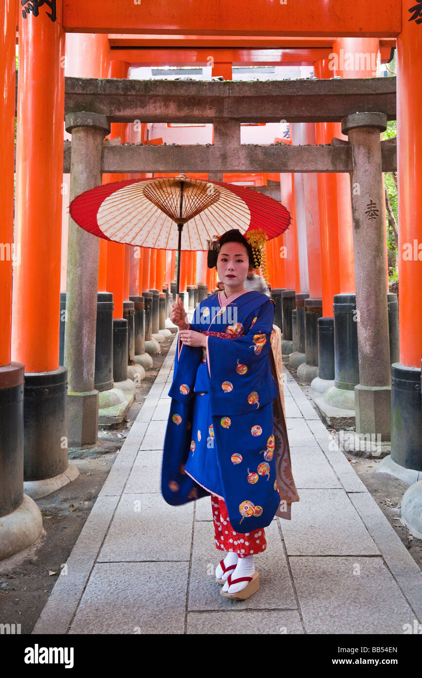 Geisha holding an ornate red umbrella, Fushimi Inari Taish, Kyoto, Kansai Region, Honshu, Japan, Asia Stock Photo