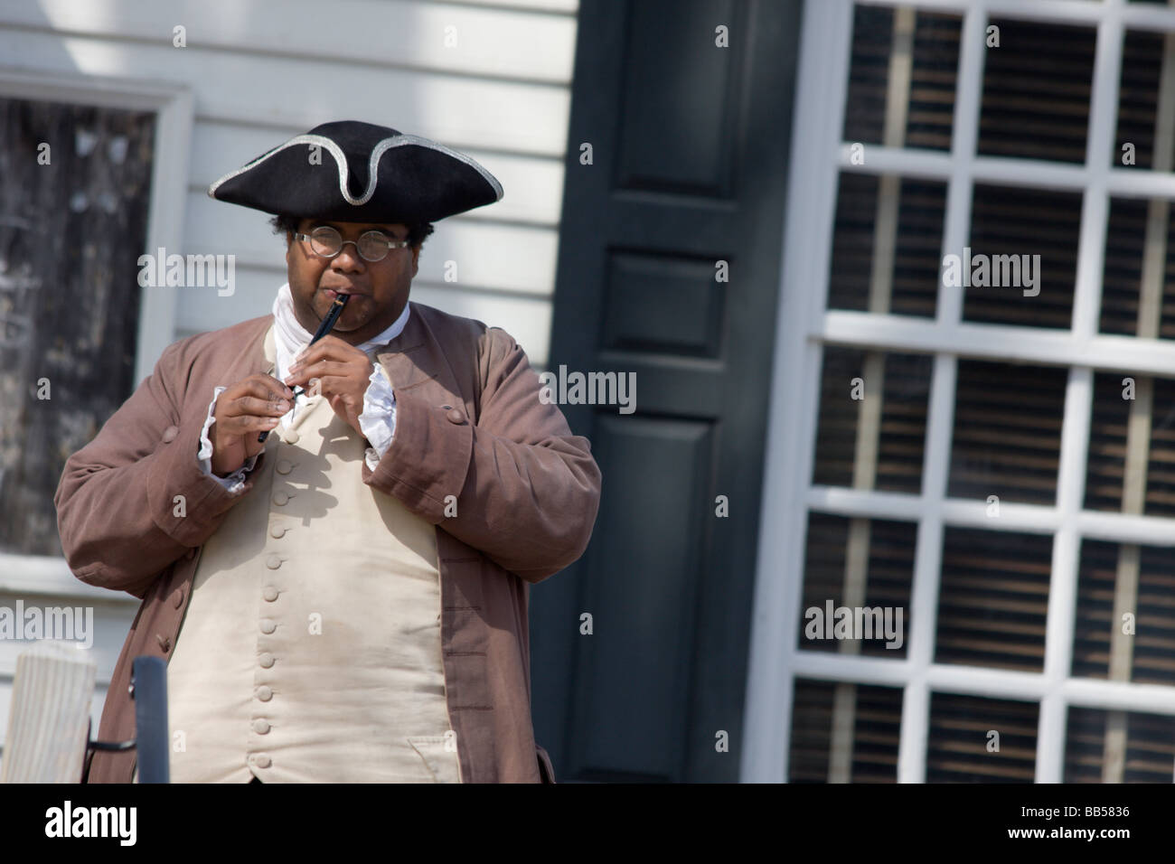 A period actor in Colonial Williamsburg, Virginia plays a flute. - Stock Image
