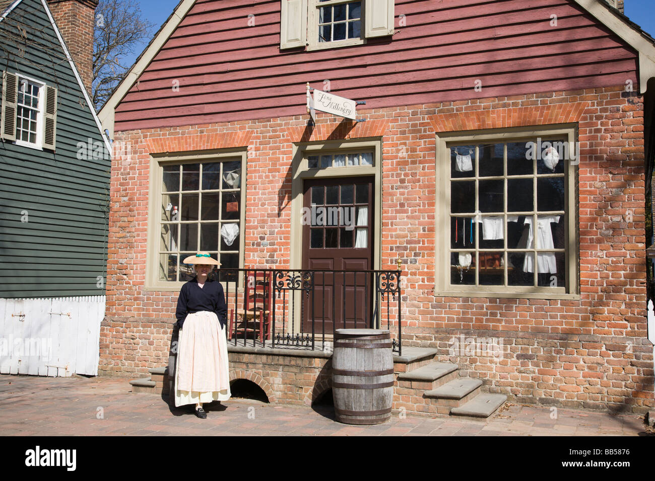 A woman welcomes visitors to the Millinery (tailoring) Shop in Colonial Williamsburg, Virginia. - Stock Image