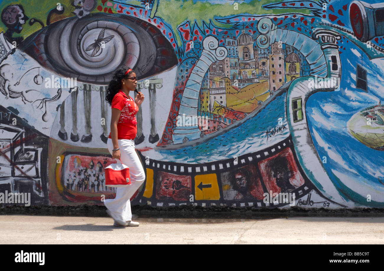Cuban lady walking down the street past painted murals on wall at