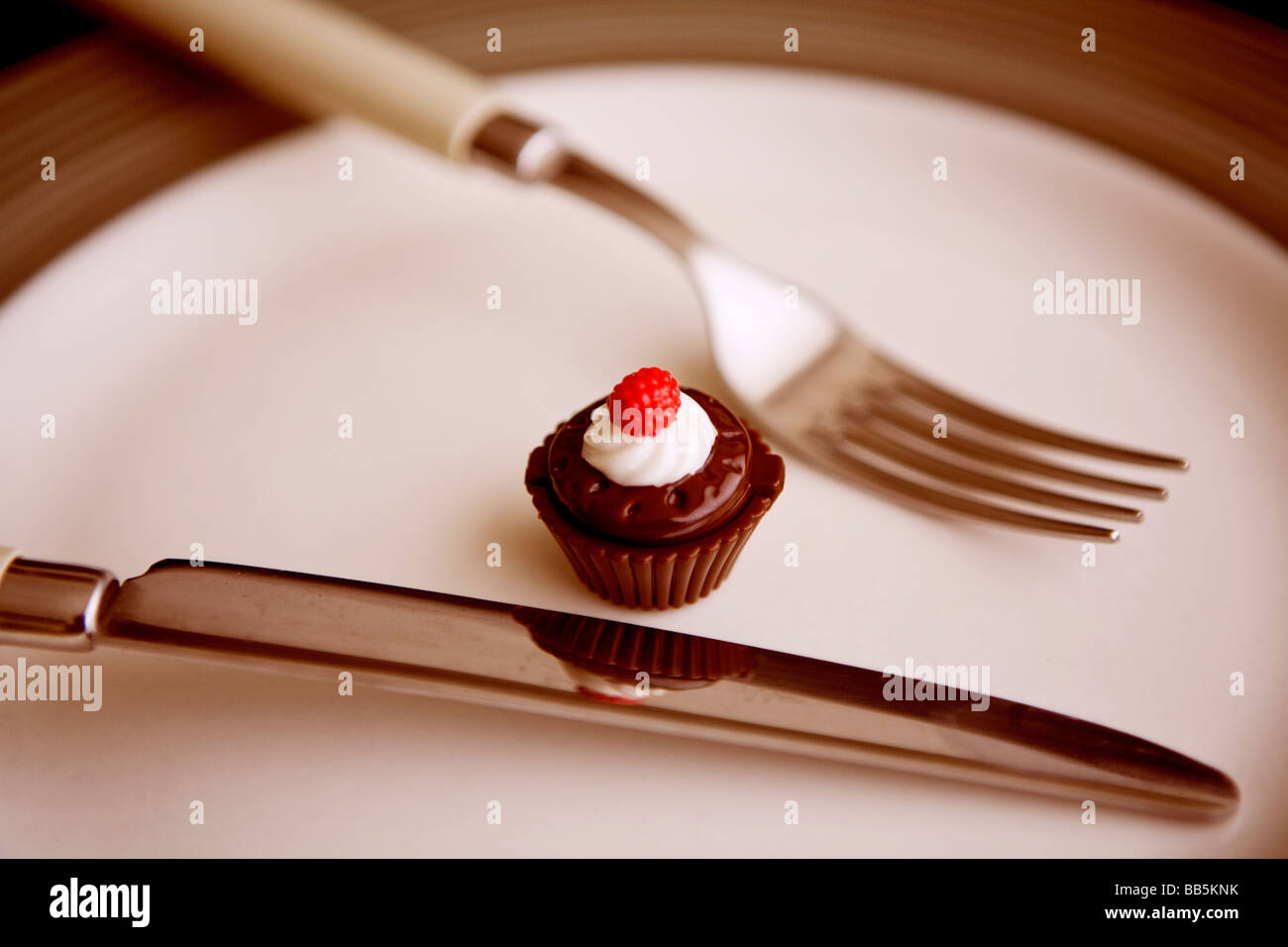 a tiny little cupcake on the plate - Stock Image