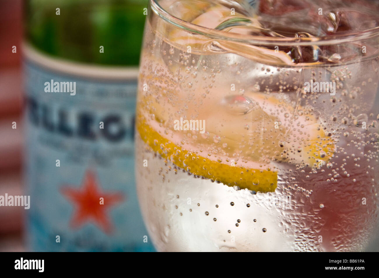 Sparkling mineral water in a glass with ice and lemon - Stock Image